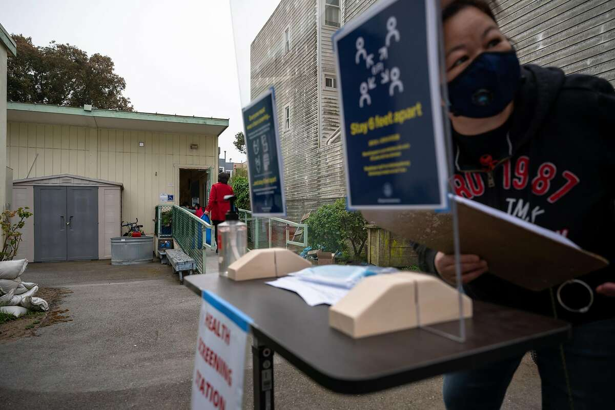 A staff member at Jefferson Early Education School in San Francisco screens and checks children in for their first day of school in April.