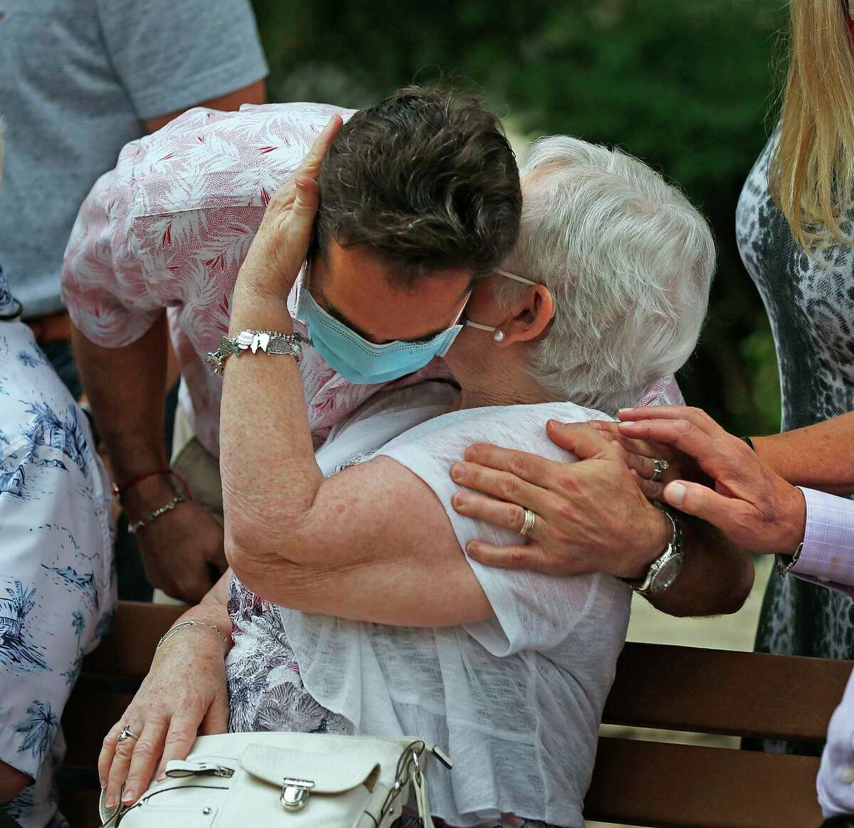 Anna Cascia, 75, is greeted by one of her sons, Mike Boucher, during the outdoor Mother's Day Mass traditionally celebrated at Our Lady of Lourdes Grotto and Tepeyac de San Antonio on Sunday.