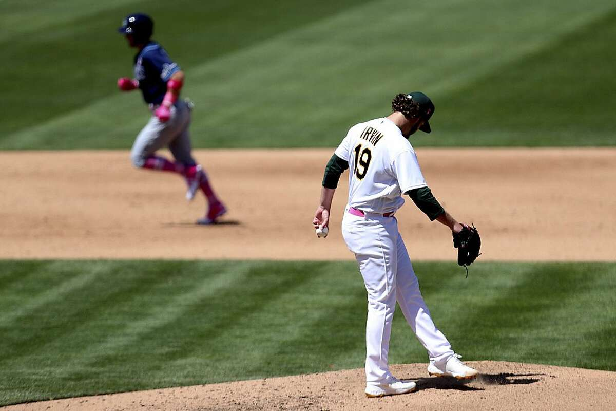Tampa Bay Rays' Mike Brosseau, left, rounds the bases after hitting a solo home run against the Oakland Athletics' Cole Irvin, right, during the sixth inning of a baseball game in Oakland, Calif., Sunday, May 9, 2021. (AP Photo/Jed Jacobsohn)