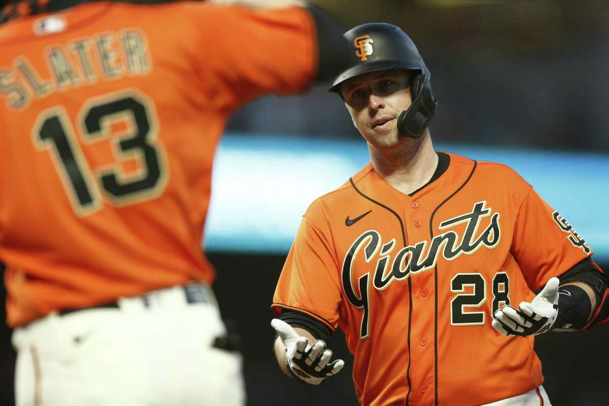 San Francisco Giants Buster Posey (28) and San Francisco Giants right fielder Austin Slater (13) celebrate in the third inning during an MLB game at Oracle Park, Friday, May 7, 2021, in San Francisco, Calif. Posey jogged back to the dugout after scoring a two-run homer.