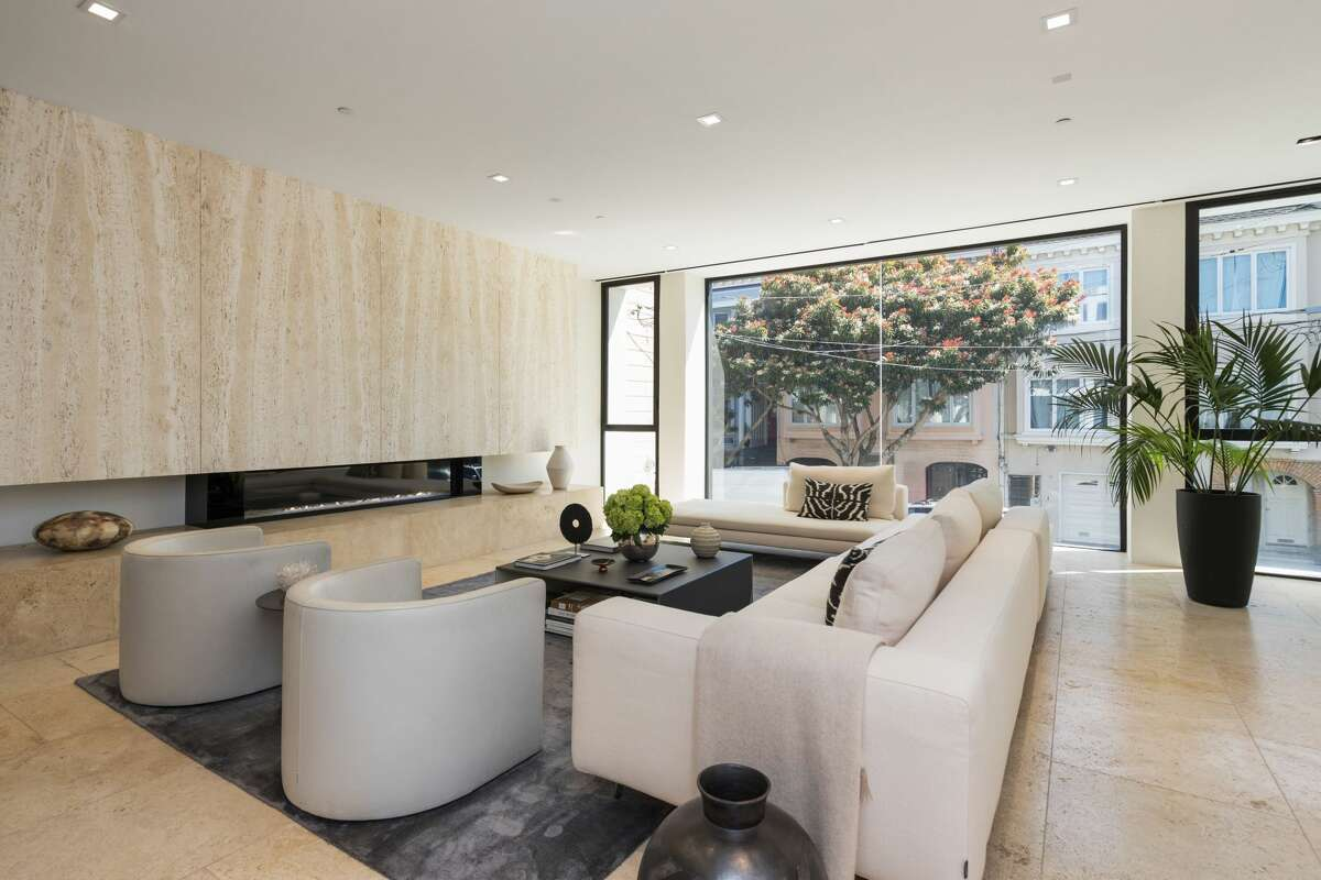 In the living room, we see the 16-foot Italian Santa Catarina travertine fireplace as well as a generous use of glass to maximize natural light.