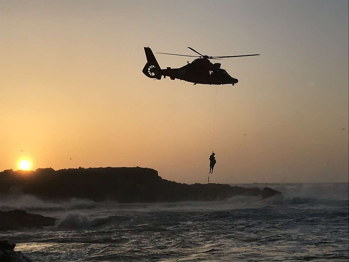 A Coast Guard helicopter hoists a stranded man from a rock outcropping at Pescadero State Beach over the weekend.