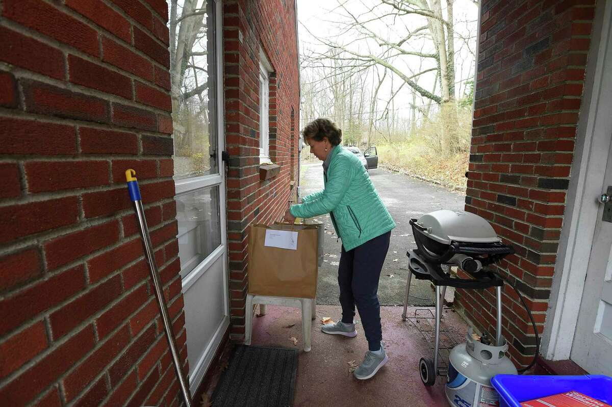 Eileen Westfahl of Stamford, one of many volunteers volunteering at SilverSource, carries bags of groceries to an elderly resident's home in the Springdale in 2020.