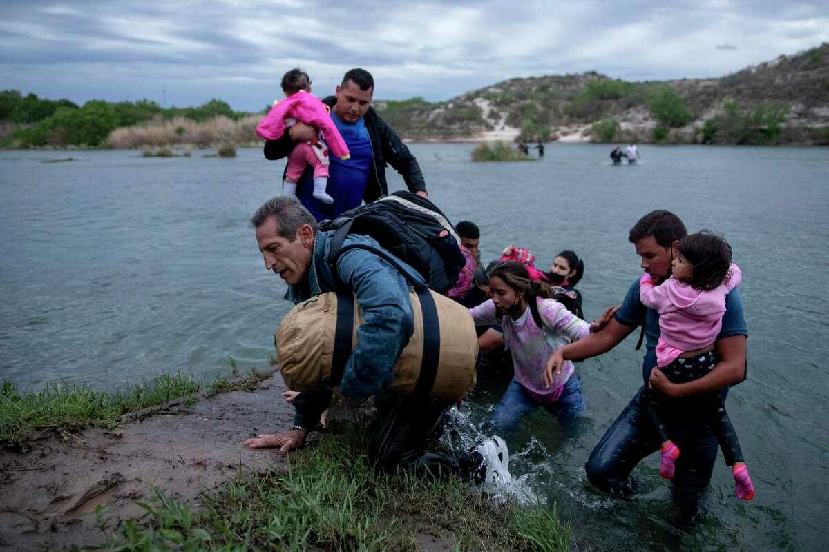 Al large group of migrants from Venezuela cross the Rio Grande near Del Rio.