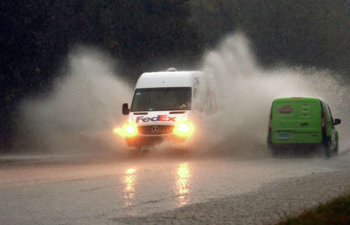 A FedEx truck splashes as water floods Park Ave during a rainstorm in Bridgeport, Conn., on Tuesday Sept. 25, 2018.