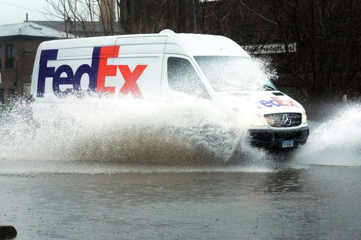 A FedEx truck drives through a flooded section of Roosevelt Drive during Monday's heavy rain in Derby, Conn. April 15, 2018.