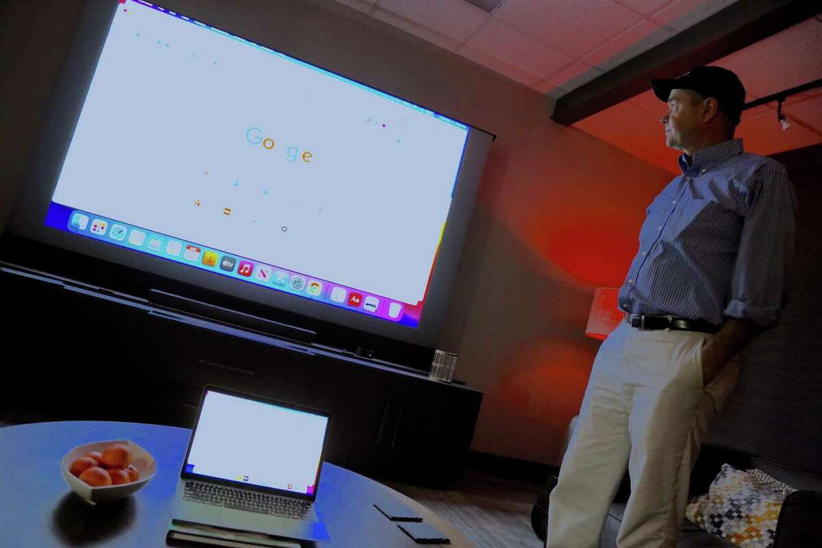 Mark Motyl, owner of Vivid-Tek, demonstrates how the 110-inch screen can be linked to your laptop and then, when not in use, lowered into the cabinet.