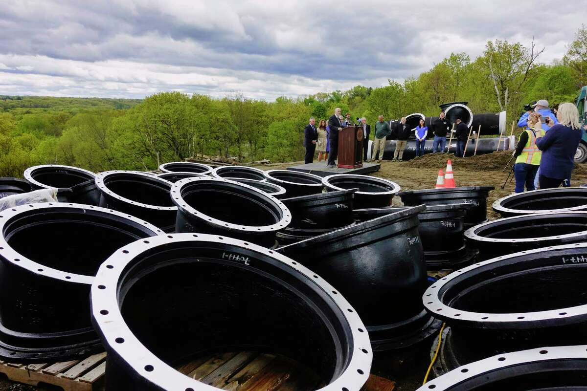 Large pieces of pipe are seen on wood pallets as Troy Mayor Patrick Madden, background, speaks during a ground breaking ceremony for a water infrastructure project on Monday, May 10, 2021, in Troy, N.Y. The project which will take multiple years, is being done to replace the water transmission lines that connect the city's Tomhannock Reservoir to the water treatment plant. (Paul Buckowski/Times Union)