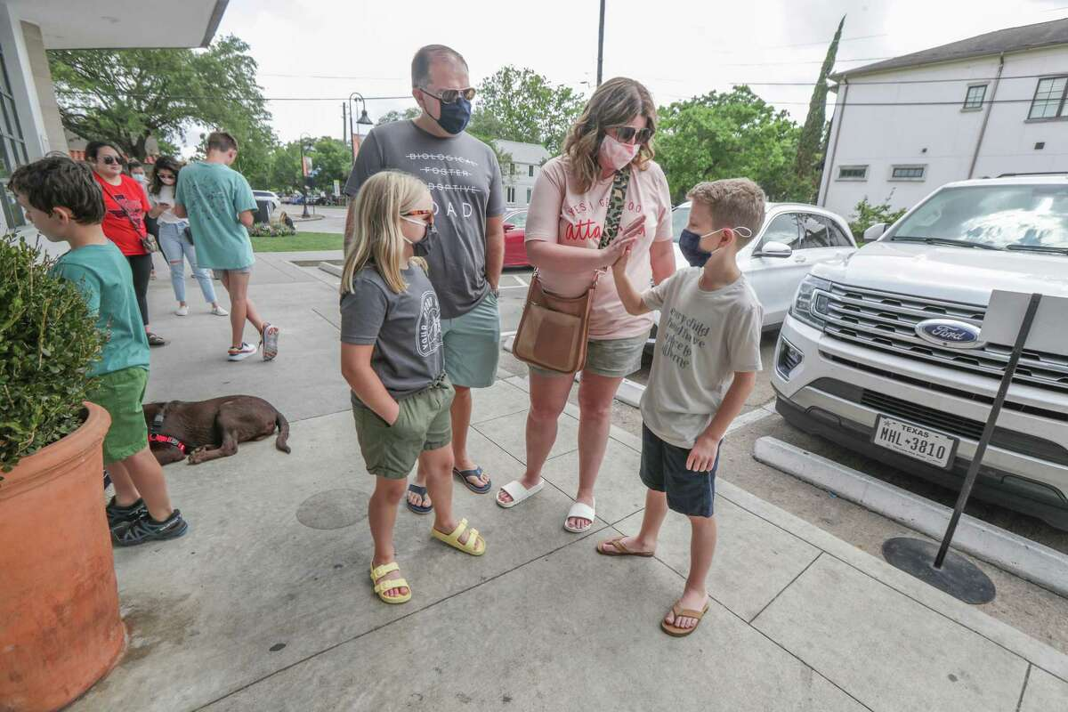 Jace Sonnier, 12, (right) gives his mom, Jaime, a high-five as father, Jon and Jordyn, 10, wait to buy ice cream Saturday, May 8, 2021, in Houston.