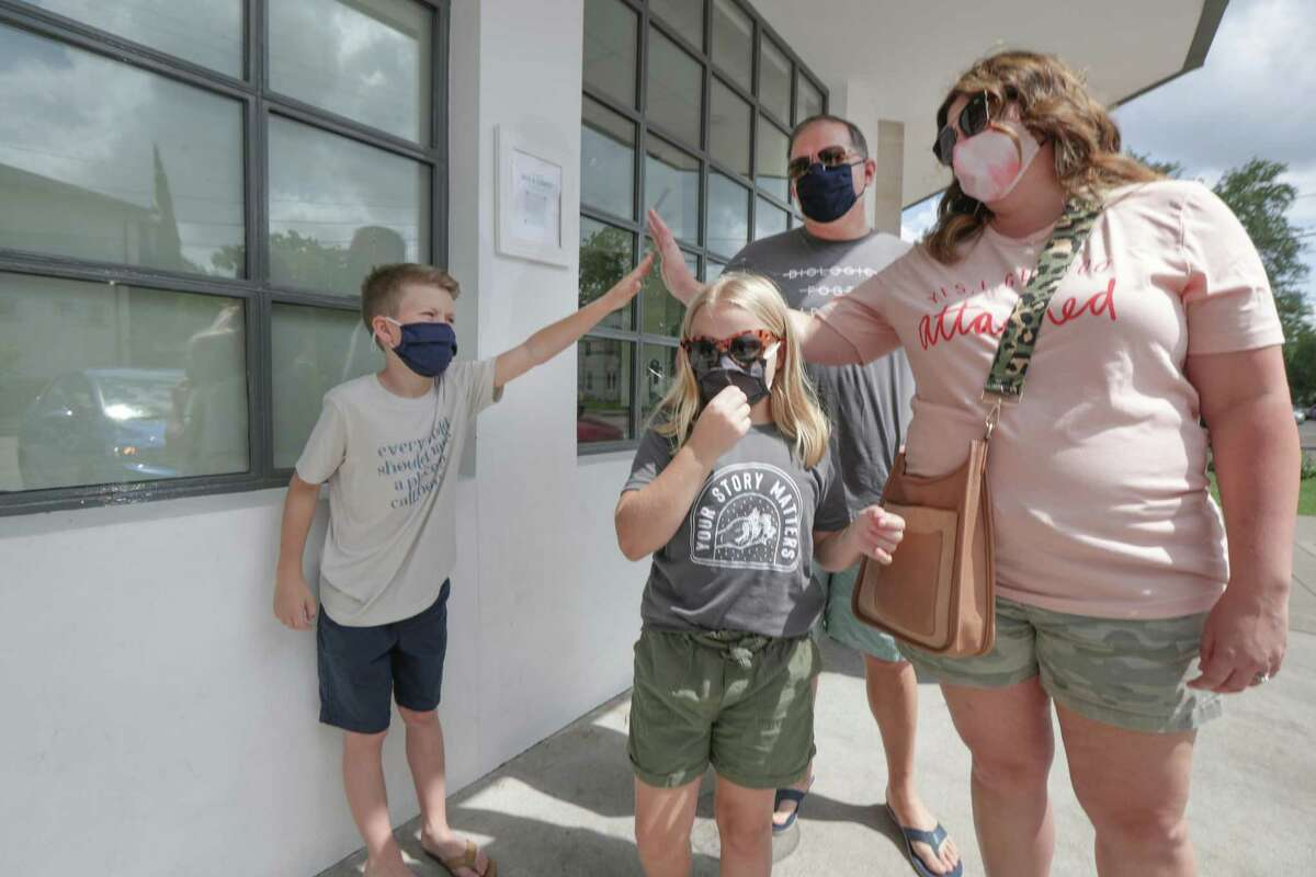 Jace Sonnier, 12, (left) gives his mom, Jaime, a high-five as father, Jon and Jordyn, 10, wait to buy ice cream Saturday, May 8, 2021, in Houston.