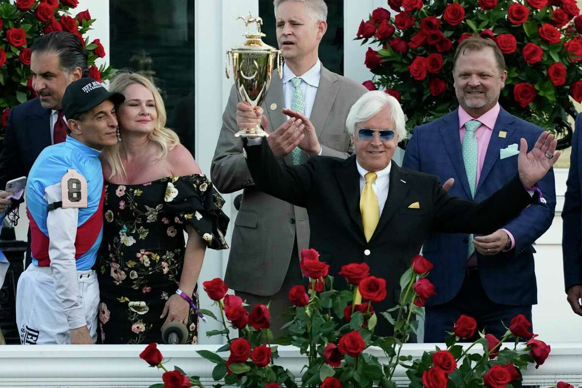Jockey John Velazquez, left, watches as trainer Bob Baffert holds up the winner's trophy after their victory with Medina Spirit in the 147th running of the Kentucky Derby at Churchill Downs, Saturday, May 1, 2021, in Louisville, Ky.