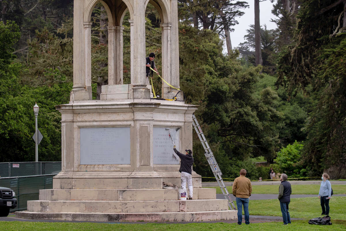 After a statue of Francis Scott Key was toppled from its pedestal in Golden Gate Park in San Francisco, crews from the city's Recreation and Park Department paint over graffiti, Saturday morning, June 20, 2020.