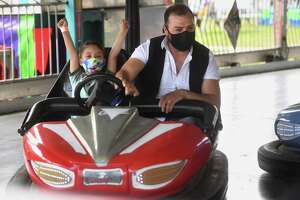 Max Vasquez, 5, of New Haven, celebrates as he rides the bumper cars with his father, Anthony, at the Coleman Brothers carnival at the Riverwalk in Shelton, Conn. on Sunday, May 9, 2021.