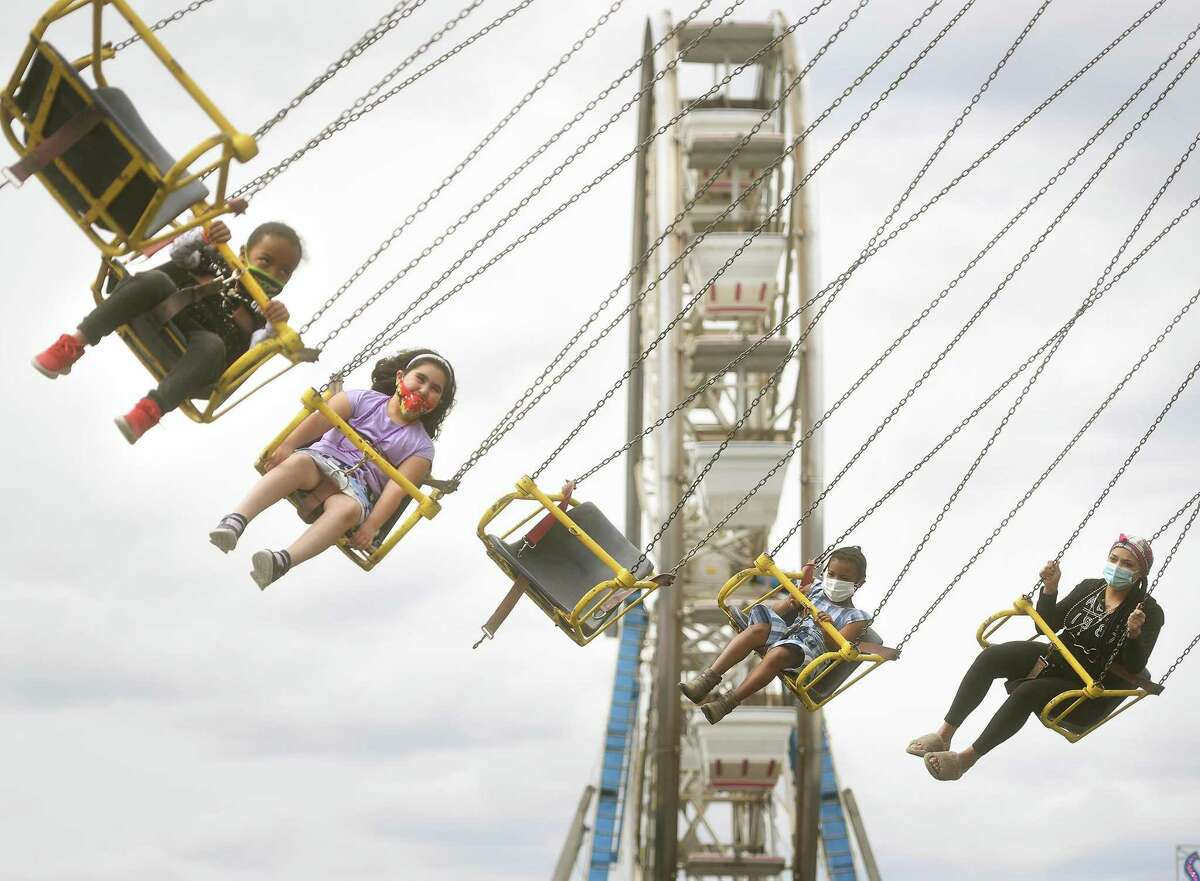 Children and adults alike enjoys one of the many rides at the Coleman Brothers carnival at the Riverwalk in Shelton, Conn. on Sunday, May 9, 2021.