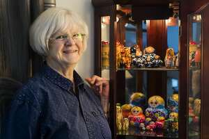 Diane Howard poses for a portrait alongside her collection of nesting dolls Tuesday, May 4, 2021 at her home in Midland. (Katy Kildee/kkildee@mdn.net)