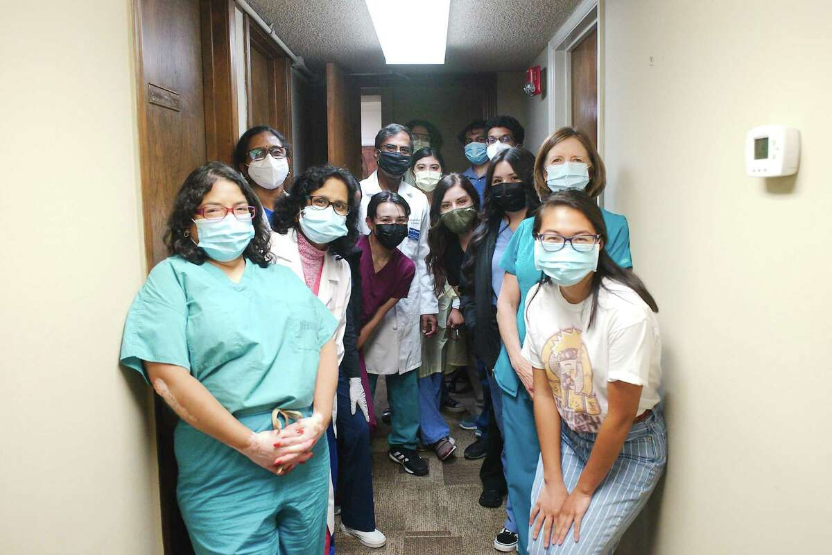Seva Clinic founder and chairman Dr. Periyanan Vaduganathan, fifth from the left, and the clinic's volunteer staff crowd into a hallway at their cramped facilities. The group and another Pearland nonprofit organization, Christian Helping Hands, are raising funds to enable a move to a proposed new building.