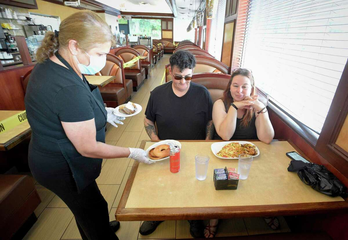 Waitress Voula Adanidou serves breakfast to travelers Mark McCray and friend Shana Johnson, both of Manchester, N.H., at Bull's Head Diner in Stamford, Conn. on June 17, 2020.