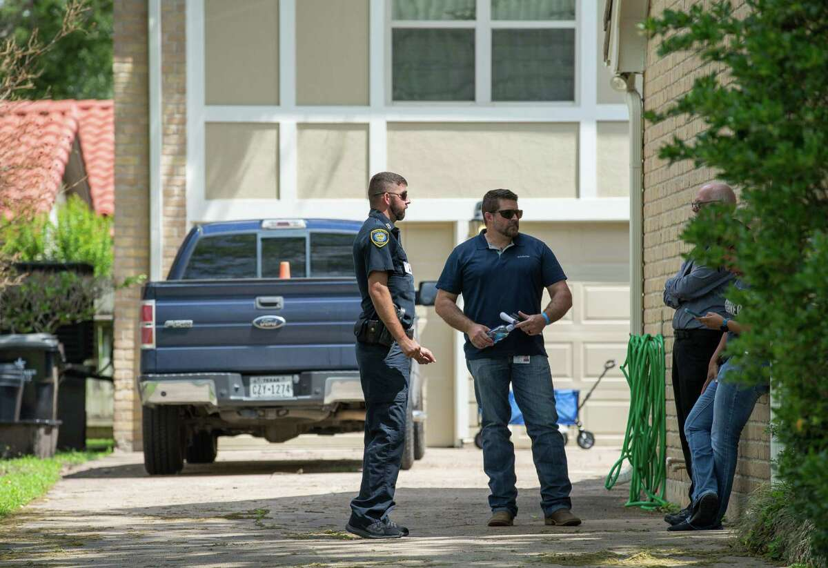 Law enforcement officials investigate the house where a tiger, which was loose last night on the 1100 block of Ivy Wall Drive, was being kept on Monday, May 10, 2021, in Houston.