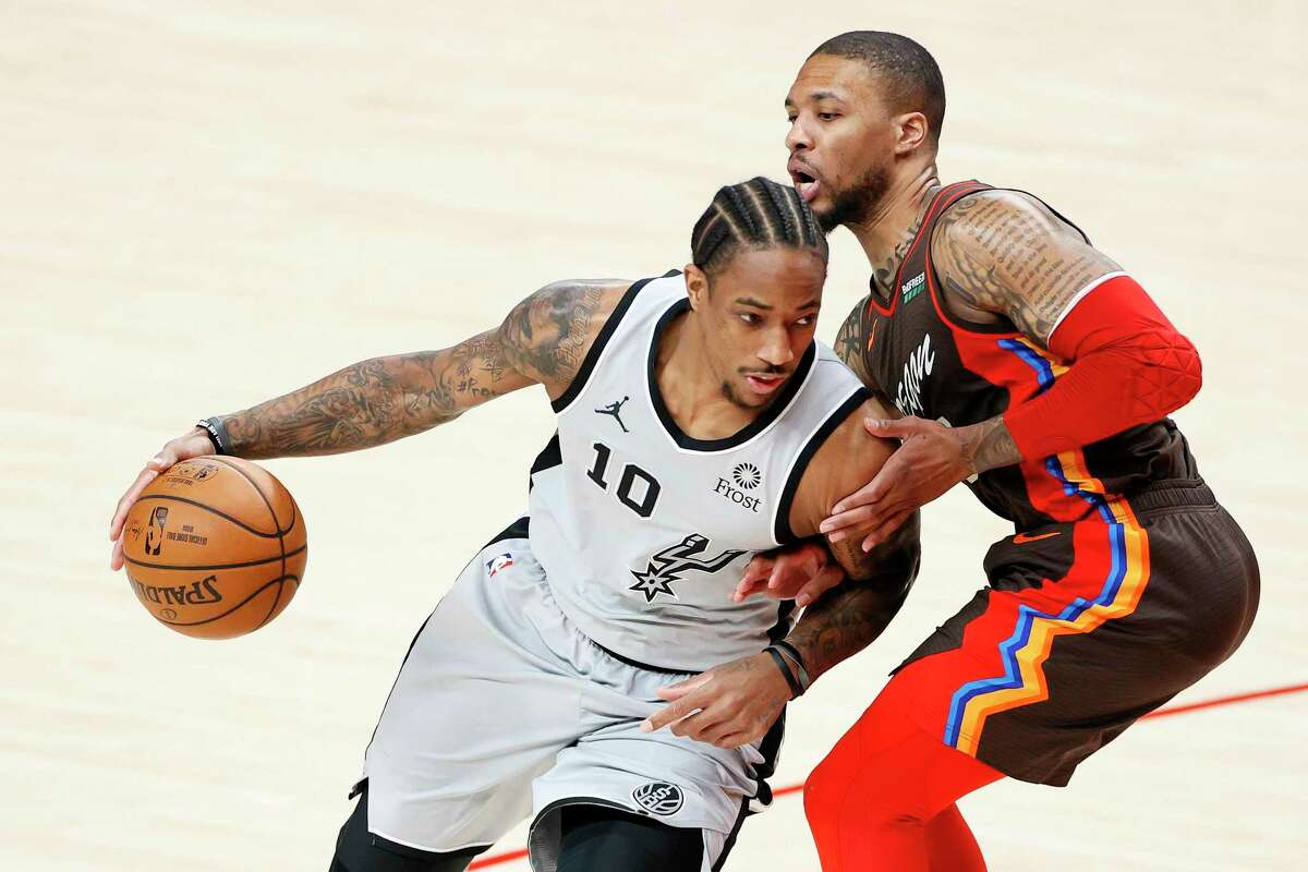 DeMar DeRozan of the Spurs dribbles against Damian Lillard of the Trail Blazers during the first quarter at Moda Center on May 8, 2021 in Portland, Ore.