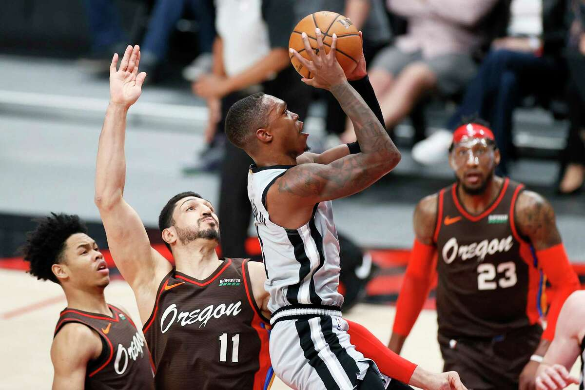 Lonnie Walker IV of the Spurs shoots against Enes Kanter (11) of the Trail Blazers during the first quarter at Moda Center on May 8, 2021 in Portland, Ore.