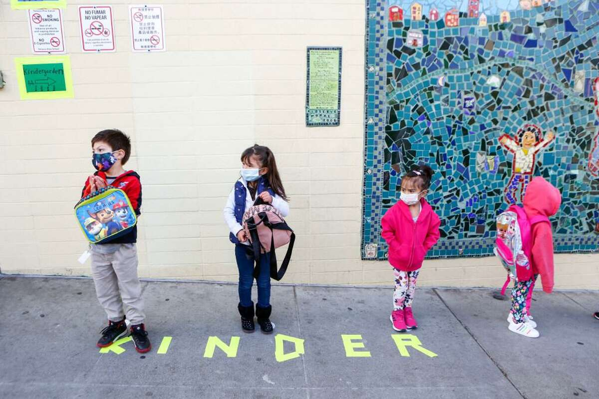 Pre-K students stand in line to check in April 12, the first day of in-person school in over a year at Bryant Elementary in San Francisco.