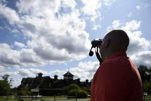 A visitor to the Audubon Society of Greenwich watches a hawk in flight.