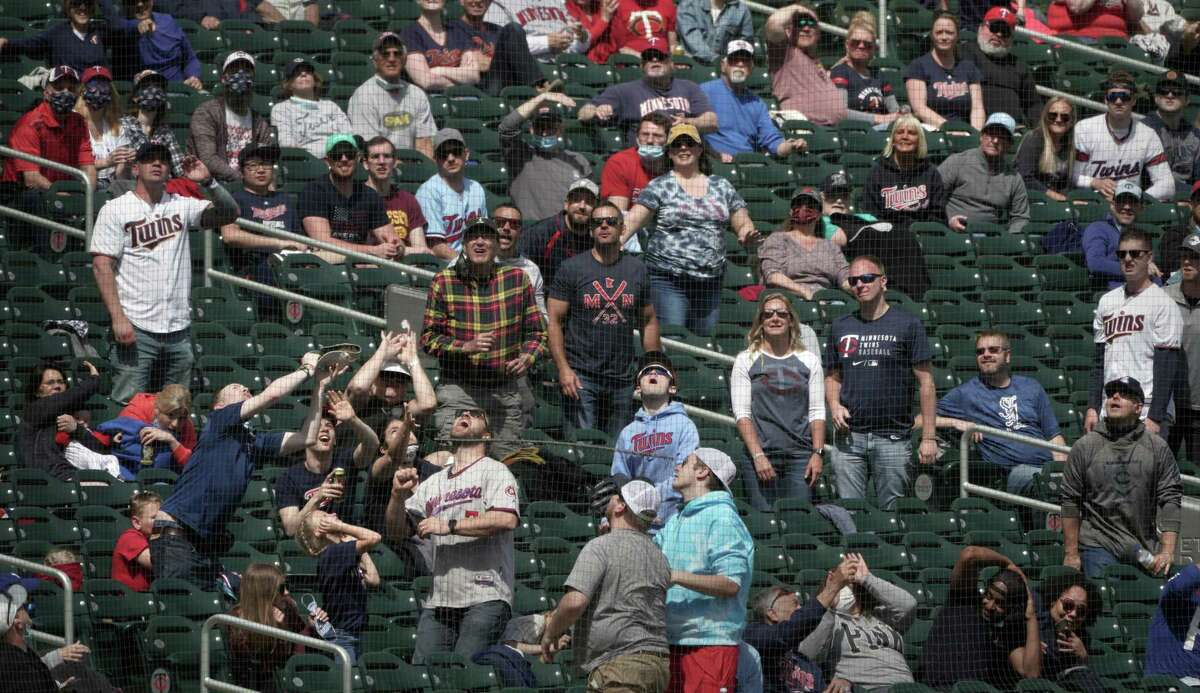 Minnesota Twins fans scramble for a foul ball in last week's game against the Texas Rangers. Although transmission is lower outdoors, it is recommended to still wear a mask if the event is crowded.