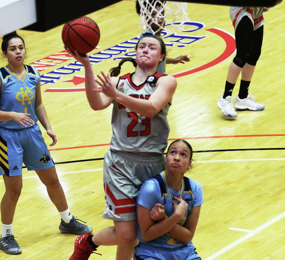 SIUE's Allie Troeckler (23) scores on her drive to the basket while getting fouled by Kansas City's Paige Bradford during a game last season at First Community Arena in Edwardsville. Troeckler will return for a fifth season with the Cougars this winter.
