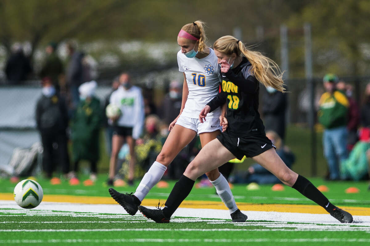 Midland's Chloe Rajewski and Dow's Klaire Caldwell battle for possession during their game Monday, May 10, 2021 at H. H. Dow High School. (Katy Kildee/kkildee@mdn.net)