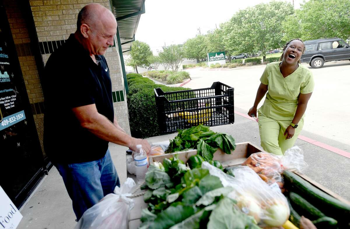 Tim Andrues with Slow Food Beaumont jokes with Yvonne Harrison as she selects produce during the group's monthly fresh produce market outside Ubi Caritas in South Park Monday. The market offers fresh fruits and vegetables for 50 cents a pound, most. of which is purchased from the Beaumont Farmer's Market. The group aims to help support local farmers while getting more fresh produce into underserved communities that fall under the umbrella of