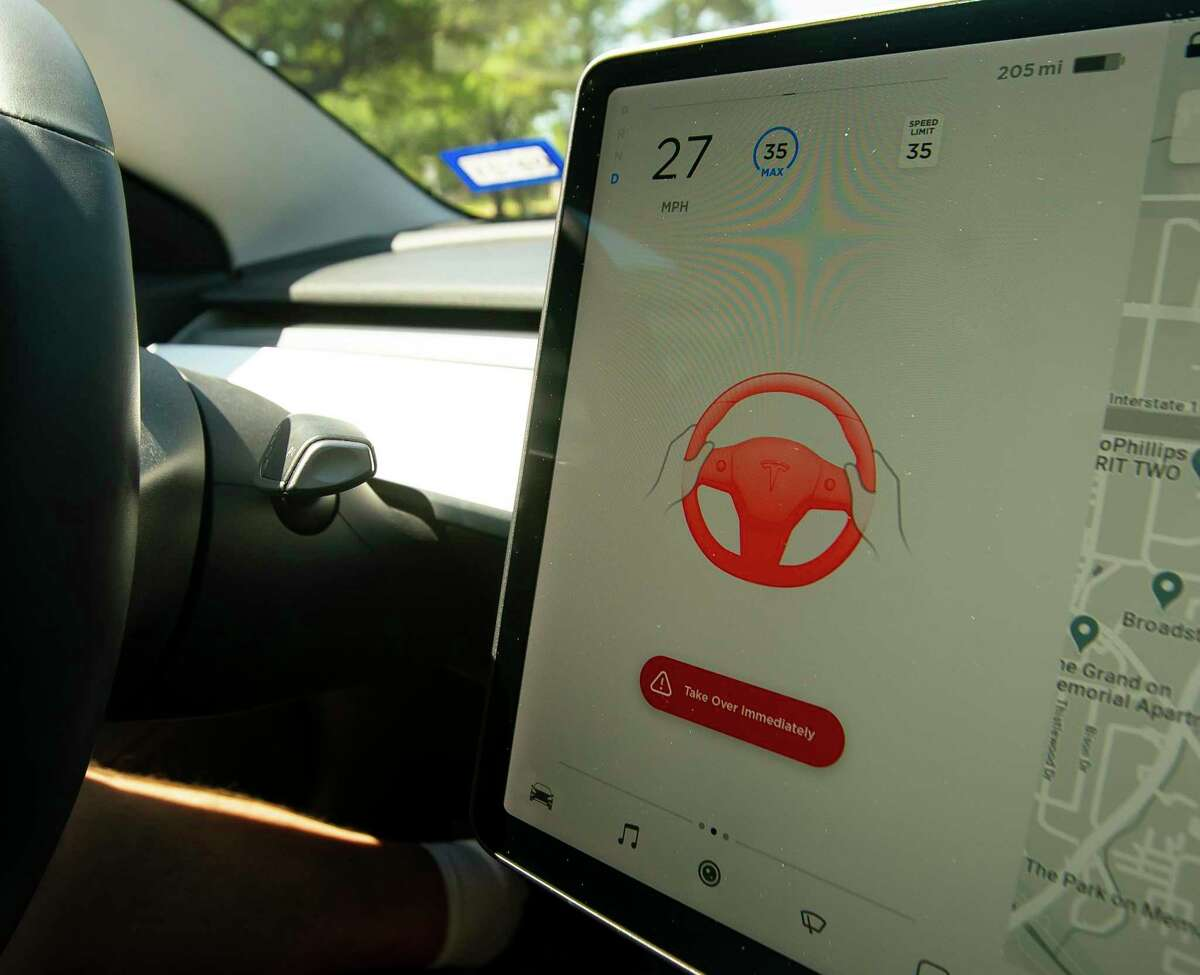 A computer warning tells Stephen Pace, founder of the Tesla Owners Group of Houston, to put his hands back on the steering wheel as he demonstrates the capabilities and limitations of the autopilot function in a Tesla Model 3 on Saturday, April 24, 2021, in Houston.