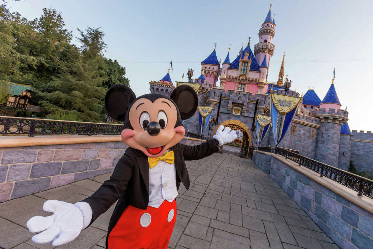 FILE - Mickey Mouse poses in front of Sleeping Beauty Castle at Disneyland Park on August 27, 2019 in Anaheim, California.