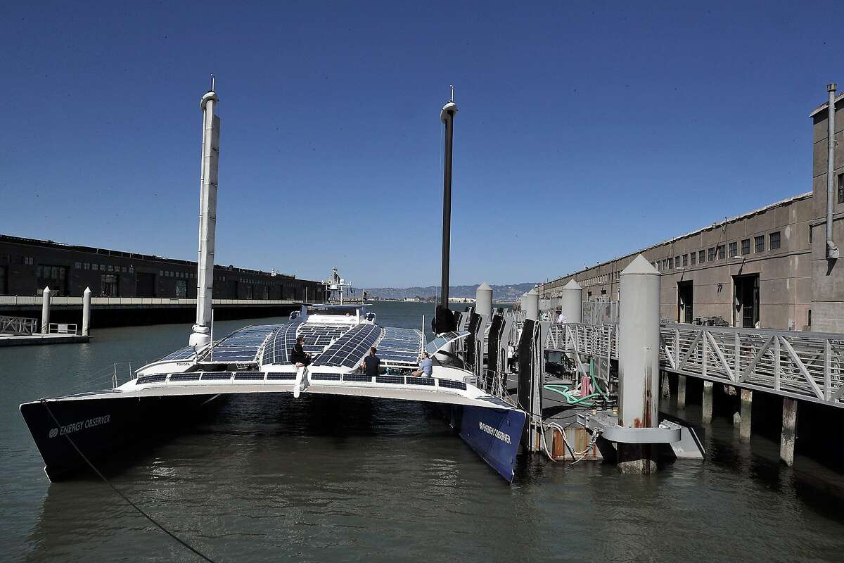 Crew members sit on the solar-cell-covered deck of the Energy Observer, which will be moored at Pier 9 in San Francisco until Friday before continuing its voyage to Hawaii.