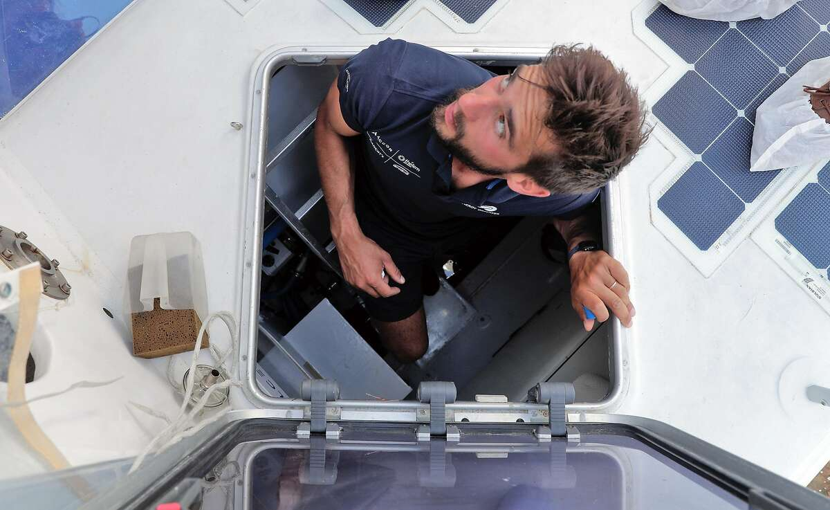 Boatswain George Conty emerges from the engine compartment. The boat also runs on hydrogen taken from seawater.