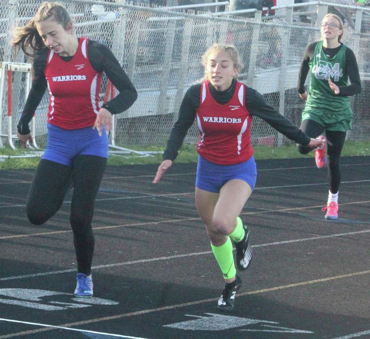 Emily Fredrick (left) and Arianna Todd of Chippewa Hills take second and first place respectively in the CSAA Gold meet 200-meter dash. (Pioneer photo/John Raffel)