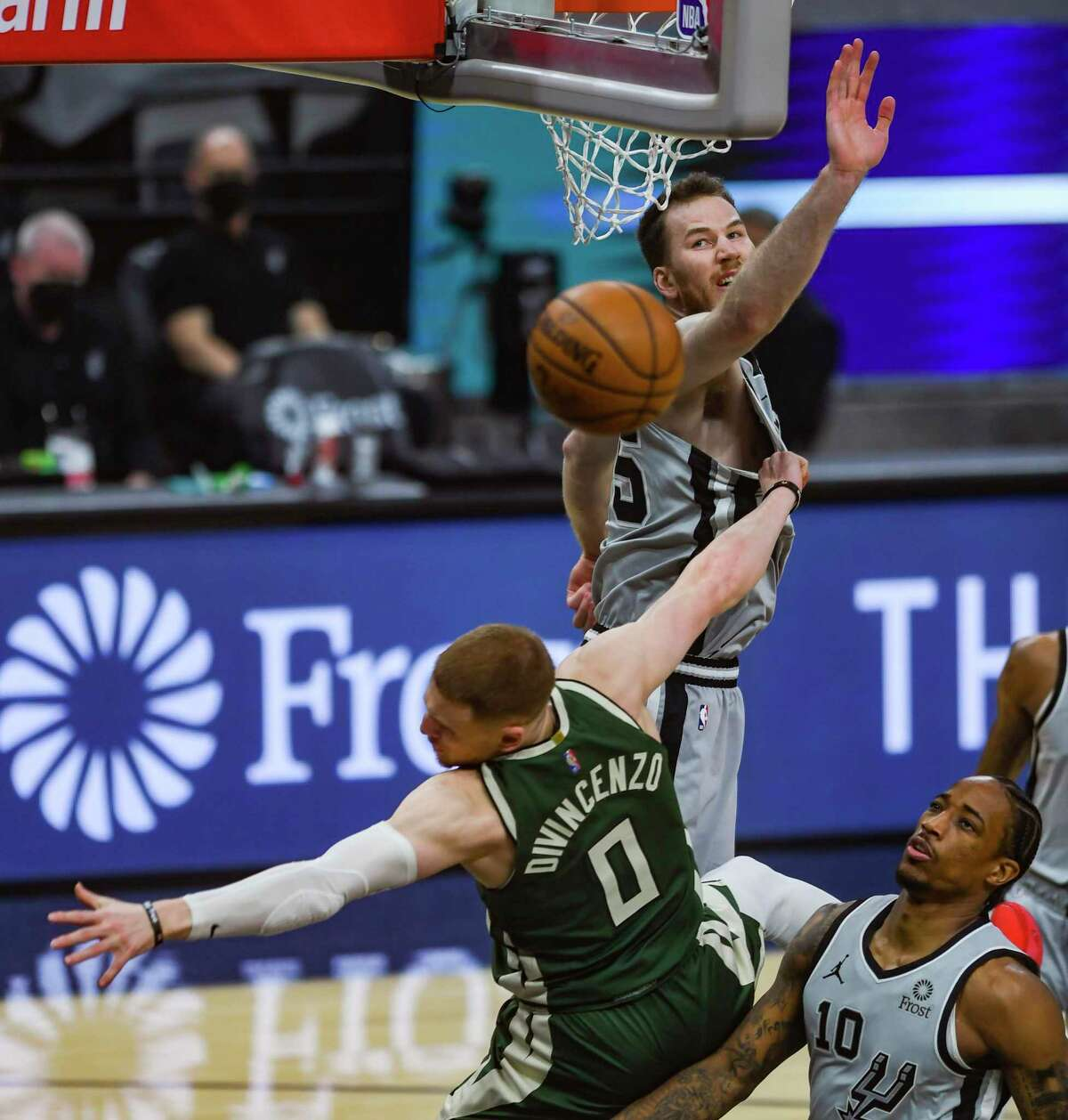 Donte DiVincenzo (0) of the Milwaukee Bucks is fouled by Jakob Poeltl, top, of the San Antonio Spurs as DeMar DeRozan, bottom right, of the Spurs, chases during first-half NBA action in the AT&T Center on Monday, May 10, 2021.