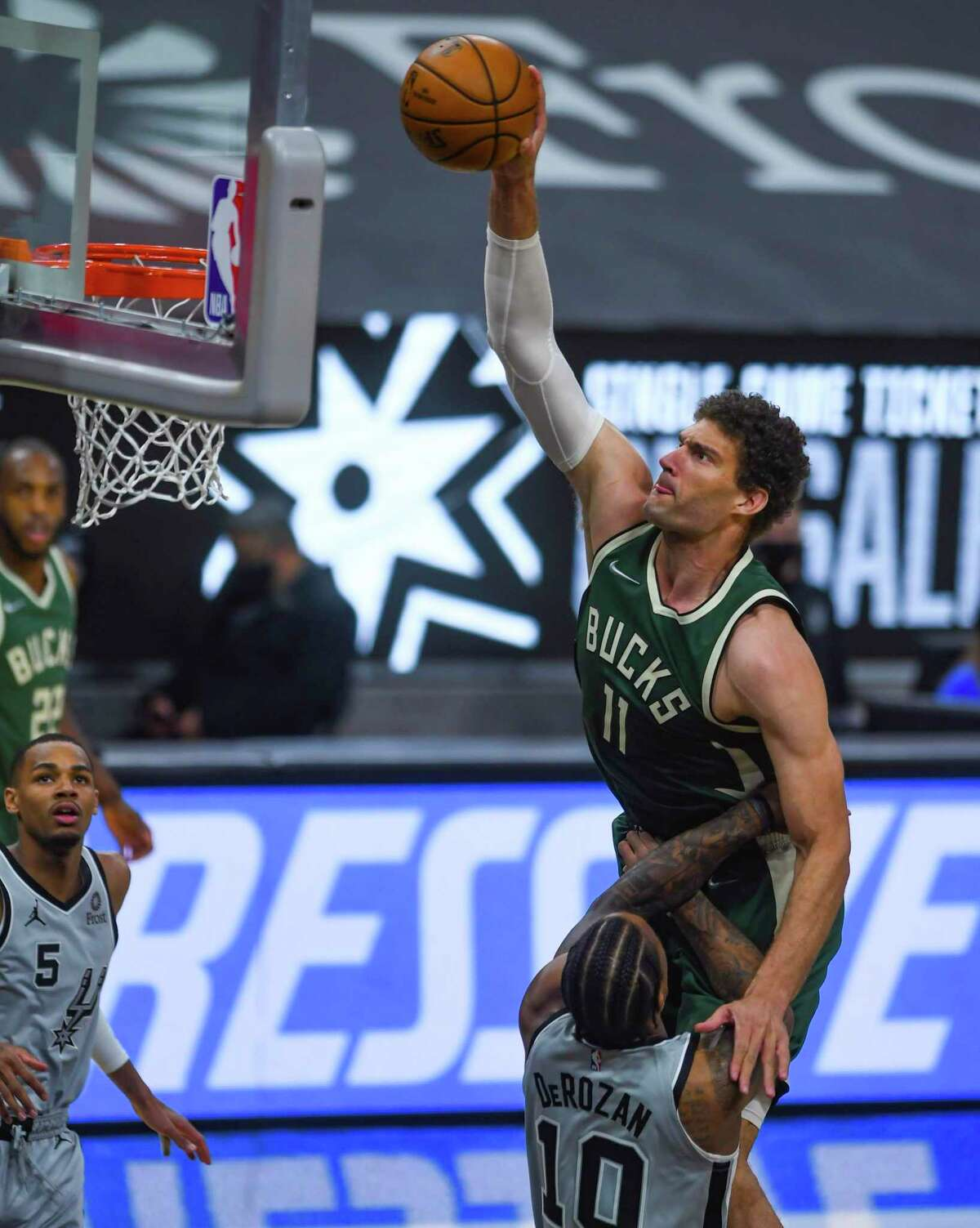 Brook Lopez of the Milwaukee Bucks dunks over DeMar DeRozan of the San Antonio Spurs during first-half NBA action in the AT&T Center on Monday, May 10, 2021.