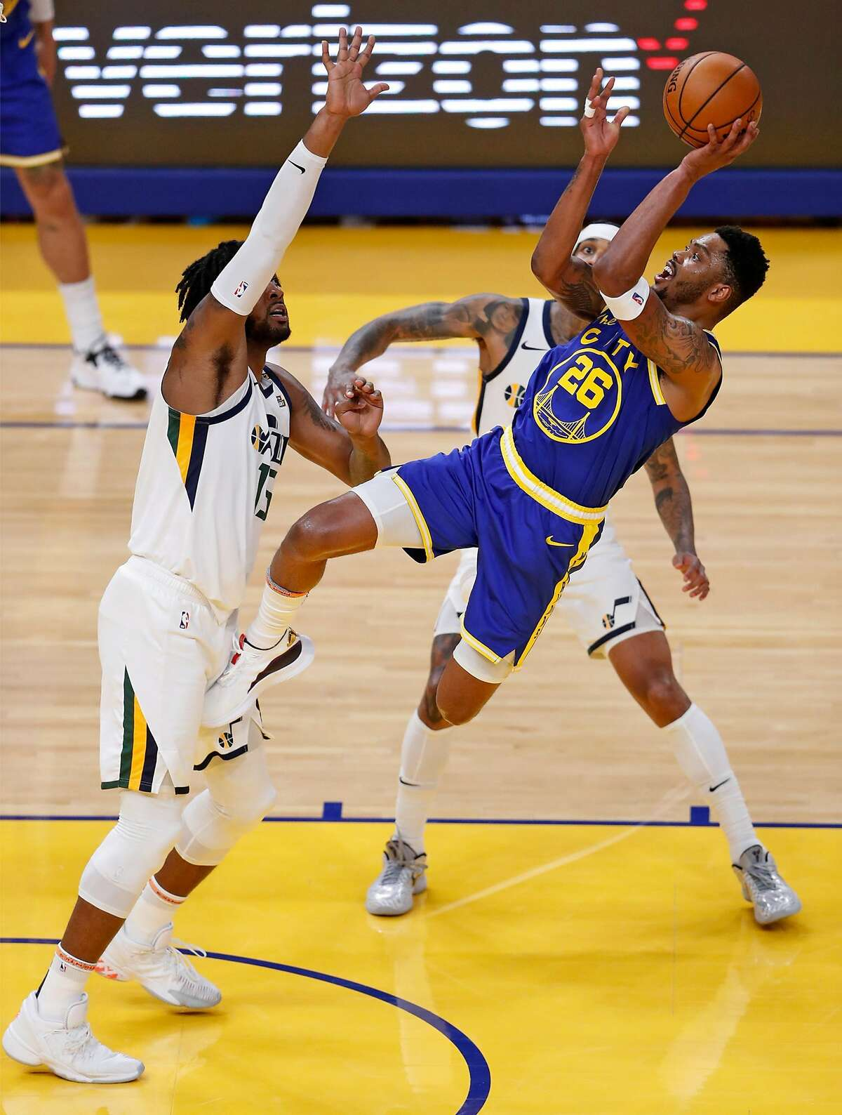 Golden State Warriors' Kent Bazemore scores while being fouled by Utah Jazz' Derrick Favors during 3rd quarter of NBA game at Chase Center in San Francisco, Calif., on Monday, May 10, 2021.