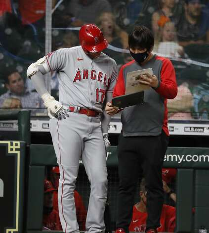 Los Angeles Angels designated hitter Shohei Ohtani (17) talks with his interpreter during the eighth inning of an MLB baseball game at Minute Maid Park, Monday, May 10, 2021, in Houston. Photo: Karen Warren/Staff Photographer / @2021 Houston Chronicle