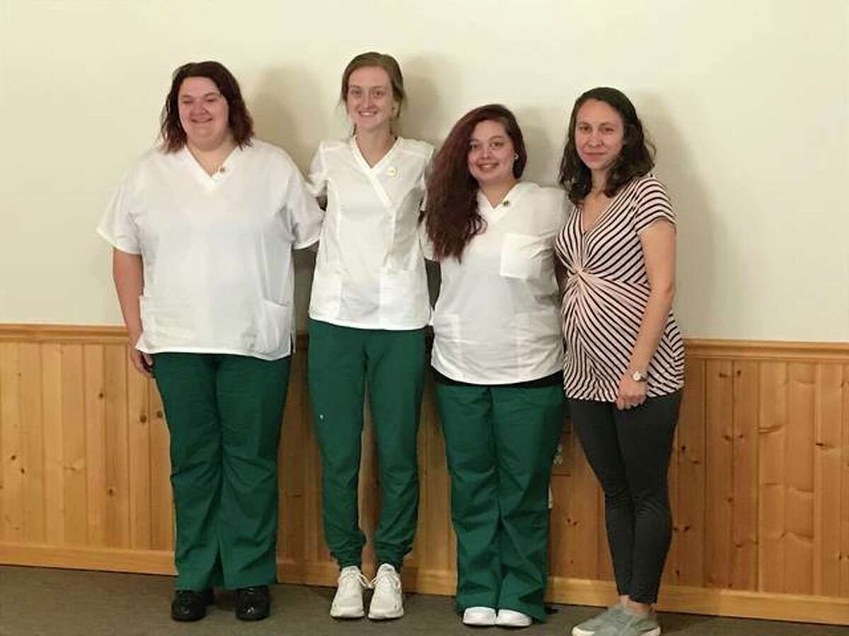 Tori Jones (from left), Macy Blentlinger and Paige Shanty received their certified nursing assistant pins from John Wood Community College instructor Erin Little.