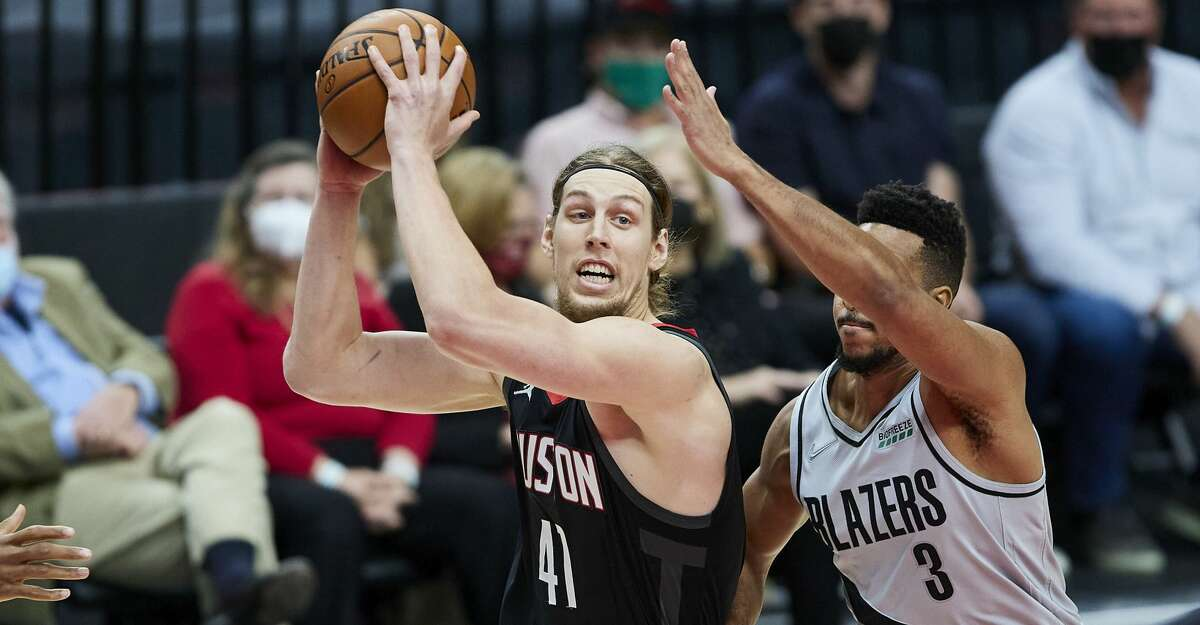 Houston Rockets forward Kelly Olynyk, left, drives to the basket past Portland Trail Blazers guard CJ McCollum during the first half of an NBA basketball game in Portland, Ore., Monday, May 10, 2021. (AP Photo/Craig Mitchelldyer)