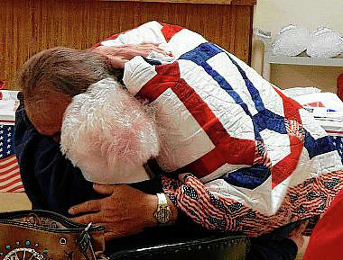 Vietnam veteran Mike Looker hugs Ida Mai Tegeder on Monday at the American Legion after receiving a Quilt of Valor in recognition of his service. Tegeder wrote to her son and his two friends, including Looker,