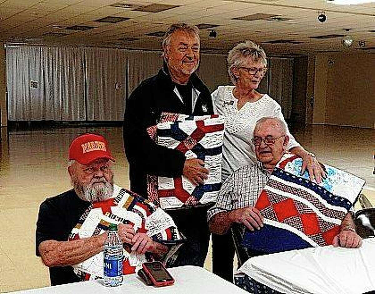 John Hembrough (from left), Mike Looker and Donald Tegeder show off their Quilts of Valor, which were made by Tegeder's sister, Evelyn Smith (back right), and presented on Monday during a gathering of friends and family at the American Legion.