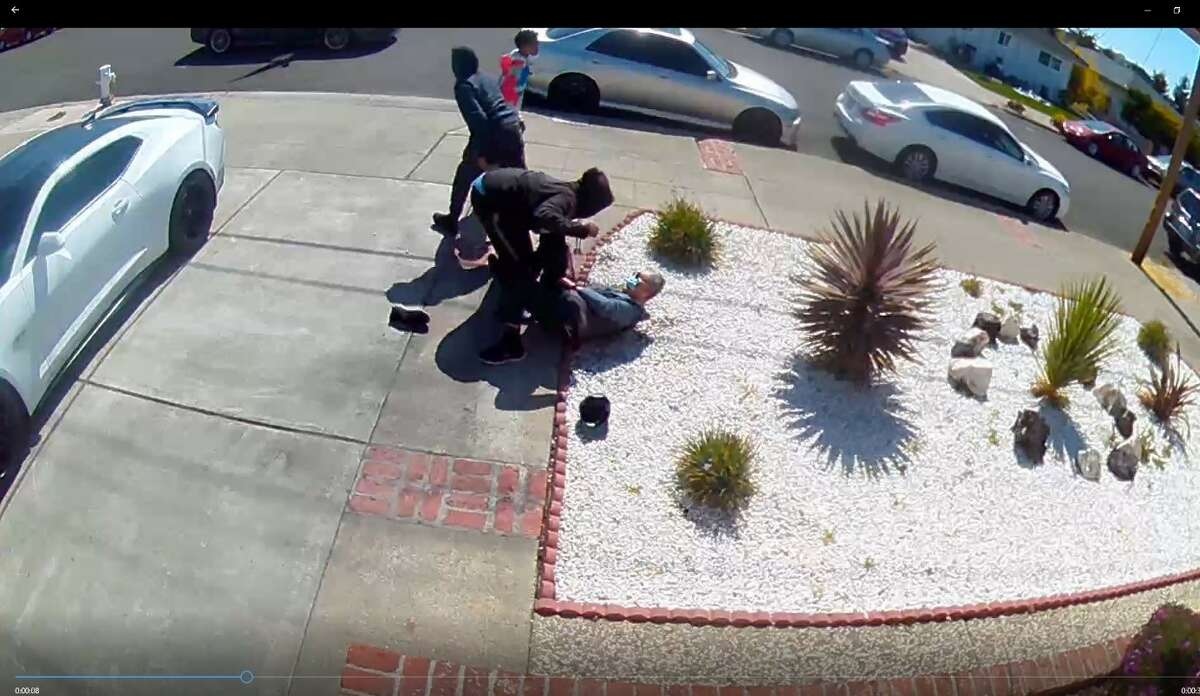 The robbery underway, showing two teens attacking an 80-year-old man.