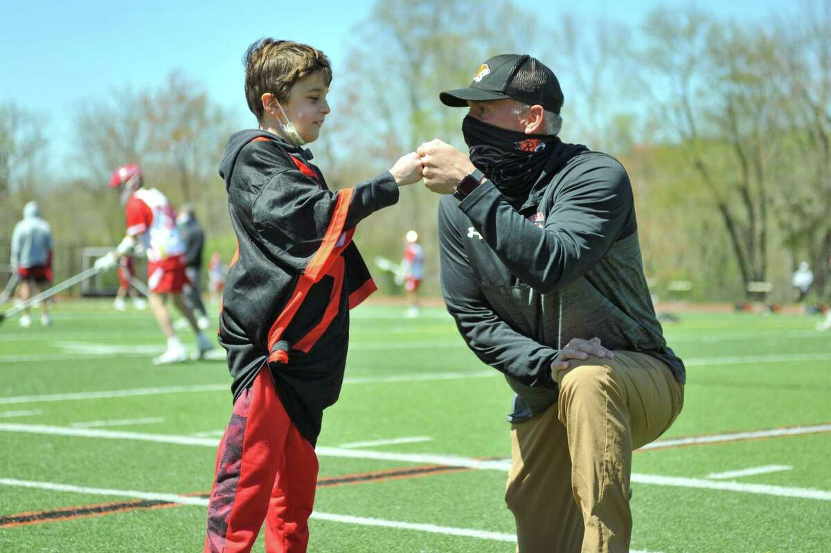 Conner Curran bumps fist with Ridgefield High School boys varsity lacrosse coach Roy Colsey, who surprised Curran with the opportunity to be honorary captain for the May 1 game.