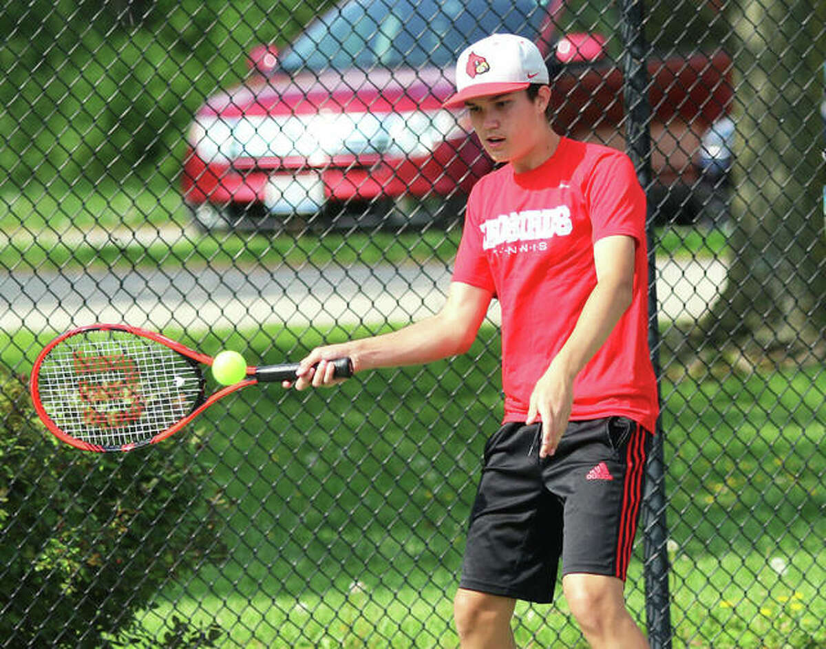 Alton's Xavier Carter, shown returning a shot in a match earlier this season, picked up a three-set victory Monday in the Redbirds' dual victory at Granite City.