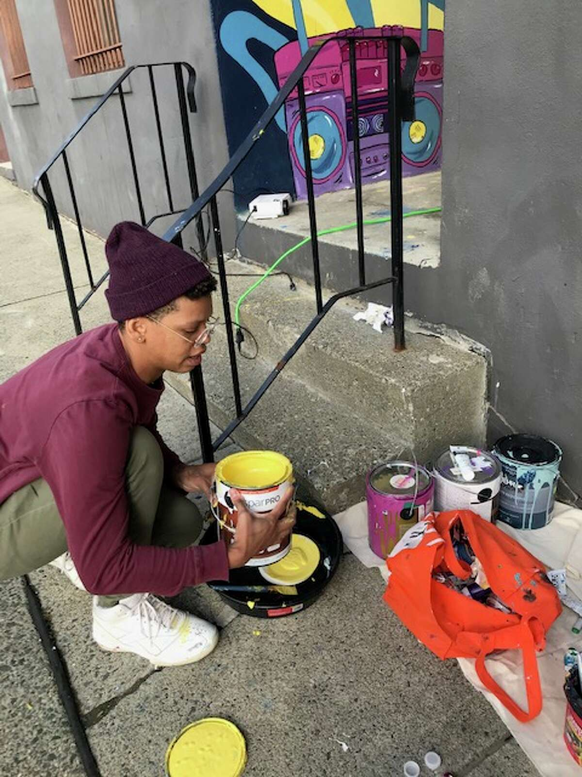 Jade Warrick mixes paint for the Troy Dance Factory mural.