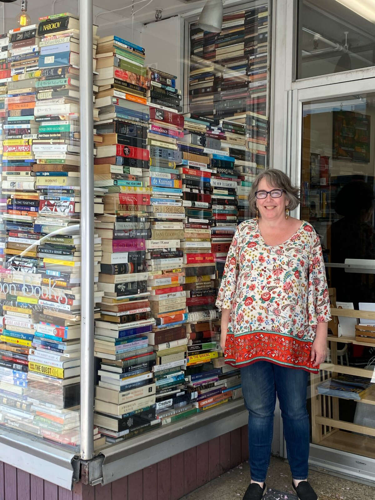 Owner Jessica DuPont stands by the window of her used bookstore in Kingston, Half Moon Books.