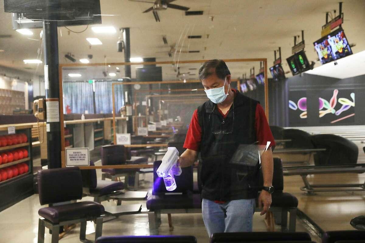 Mike Leong, owner Bel Mateo Bowl in San Mateo, sanitizes a bowling lane using a Kik-Shot sanitizer on March 16, 2021.