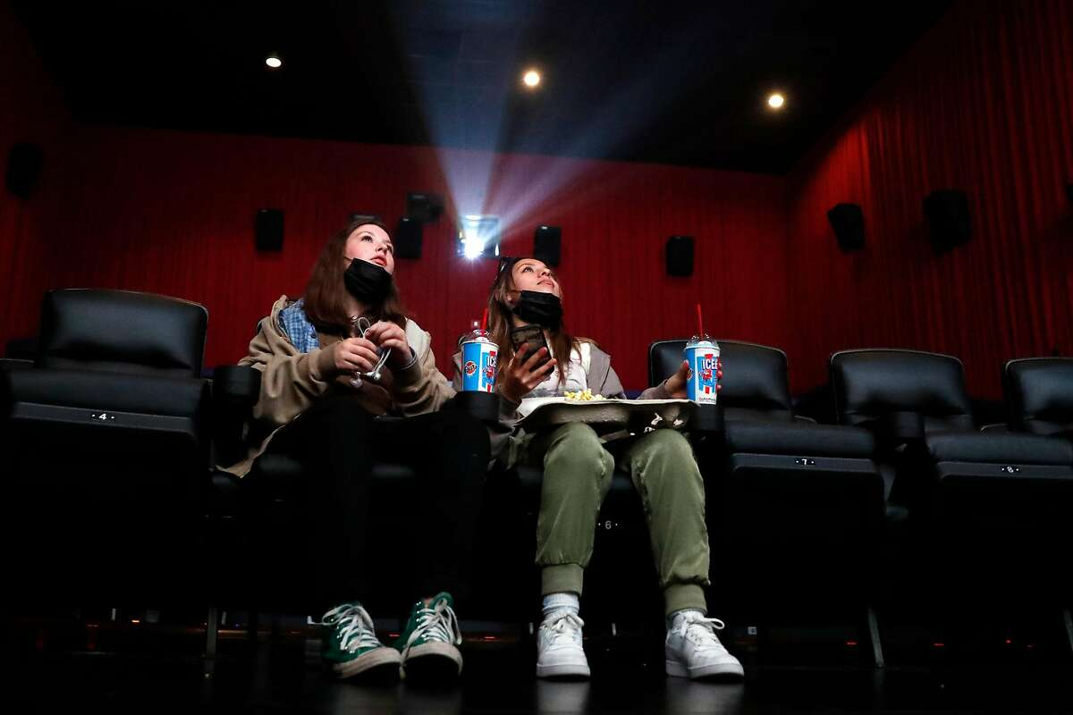 Bella Miraglia (left) and Grace Lazar watch the screen during a private watch party of